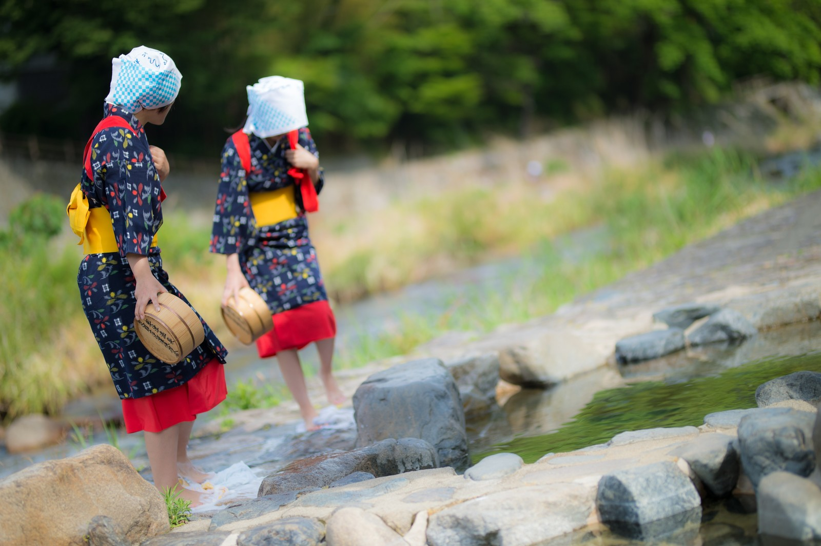 「赤い腰巻きと黄色い帯をつけた姉さんがフミフミ洗濯(足踏み洗濯)」の写真