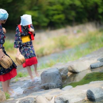 赤い腰巻きと黄色い帯をつけた姉さんがフミフミ洗濯(足踏み洗濯)の写真