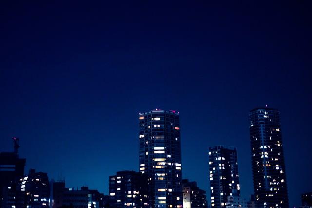 部屋の明かりがまばらな高層マンションの写真