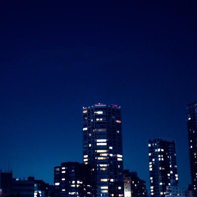 「部屋の明かりがまばらな高層マンション」の写真素材