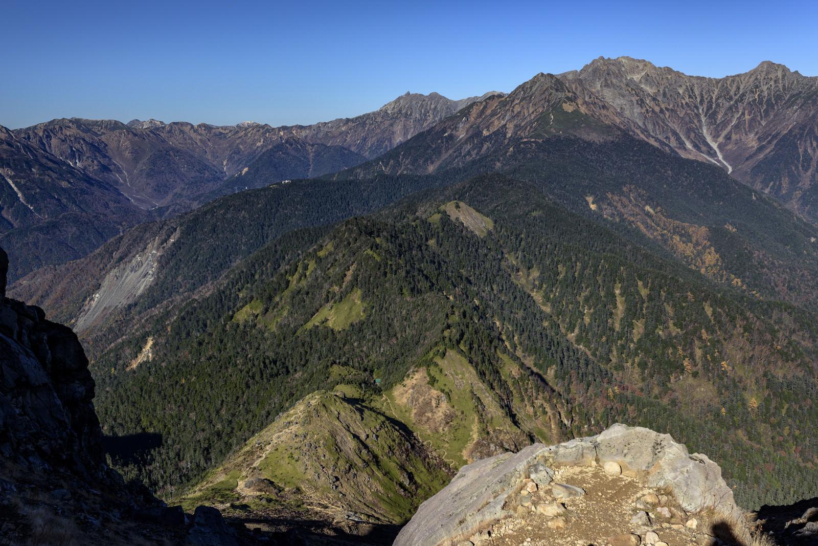 「焼岳の山小屋と遠方の槍ヶ岳(やりがたけ)」の写真