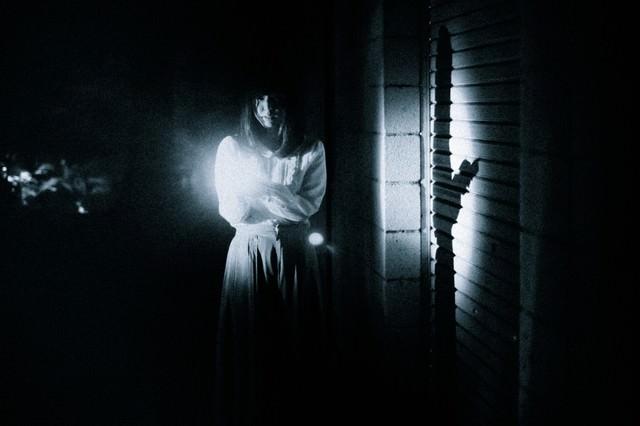 恐る恐る暗闇を歩く女性の姿の写真
