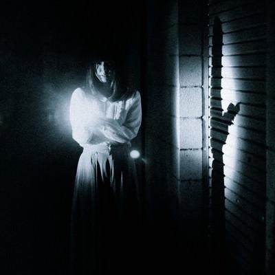 「恐る恐る暗闇を歩く女性の姿」の写真素材