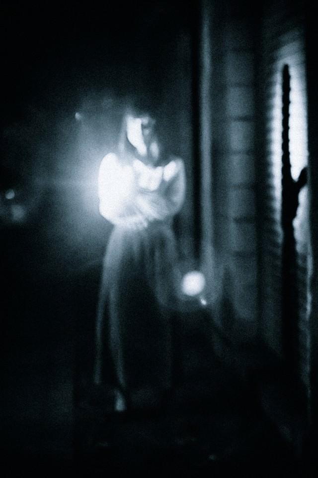 懐中電灯で正面を照らす女性の姿の写真