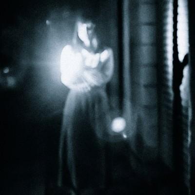 「懐中電灯で正面を照らす女性の姿」の写真素材