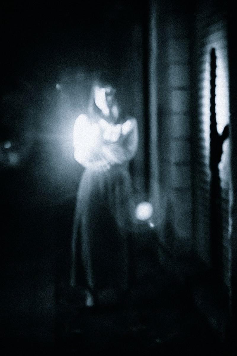 「懐中電灯で正面を照らす女性の姿」の写真[モデル:さとうゆい]