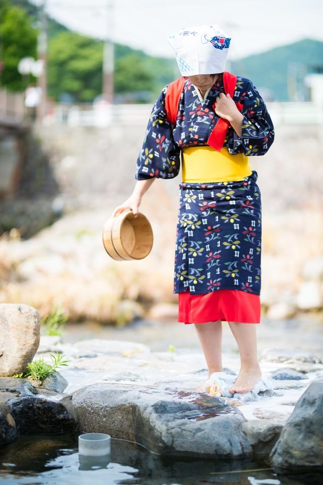 「吉井川の側で流れる温泉を使って足踏み洗濯する様子」のフリー写真素材