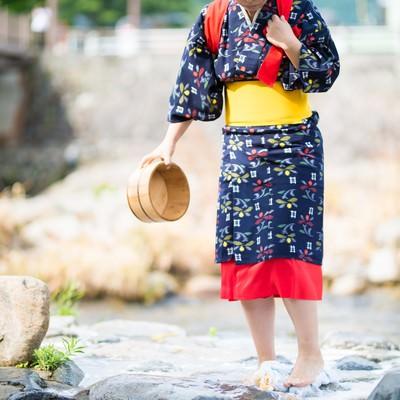「吉井川の側で流れる温泉を使って足踏み洗濯する様子」の写真素材