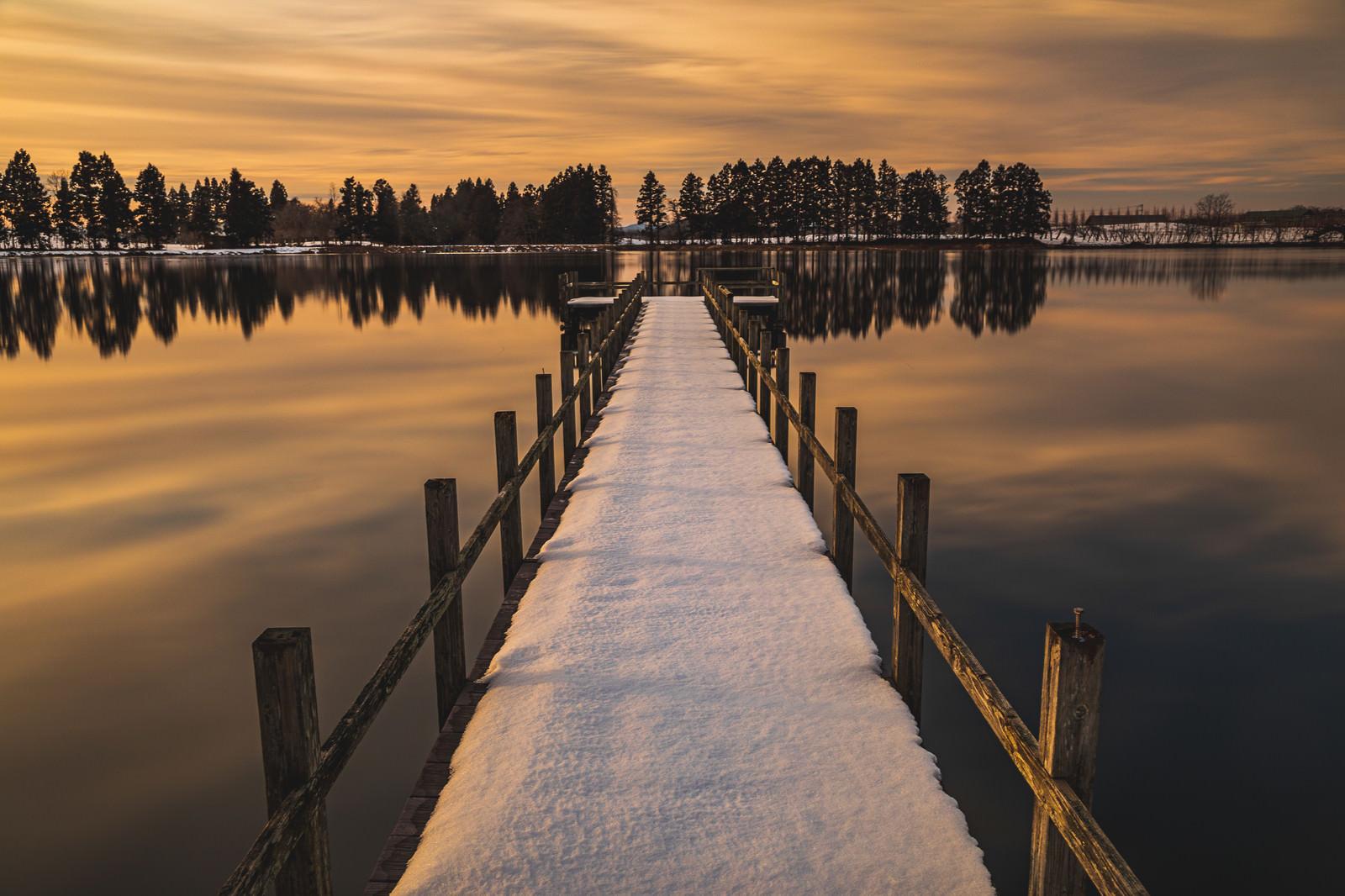 「夕焼けに染まる湖面と残雪の桟橋」の写真