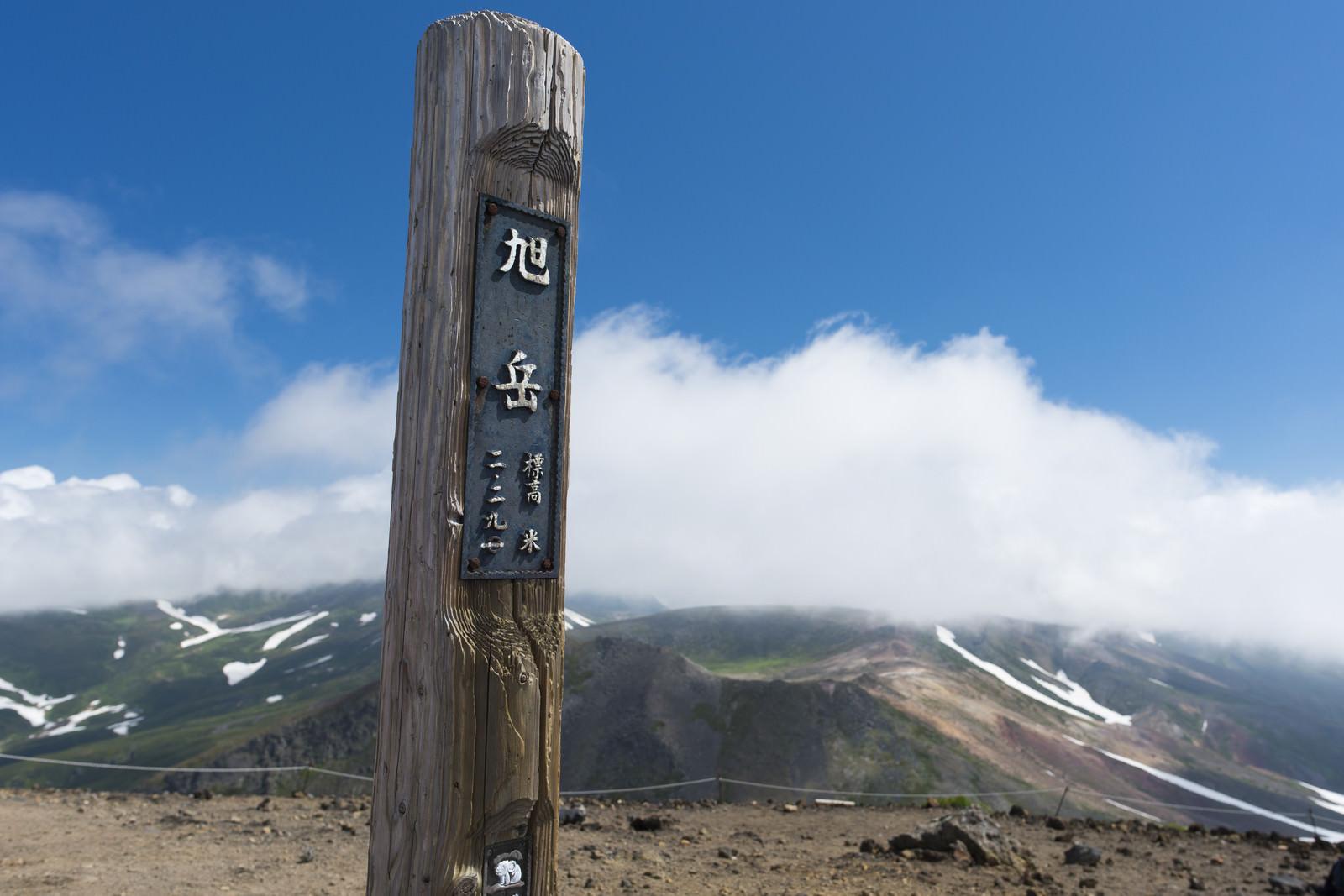 「背景に雲が流れる旭岳山頂の木碑」の写真