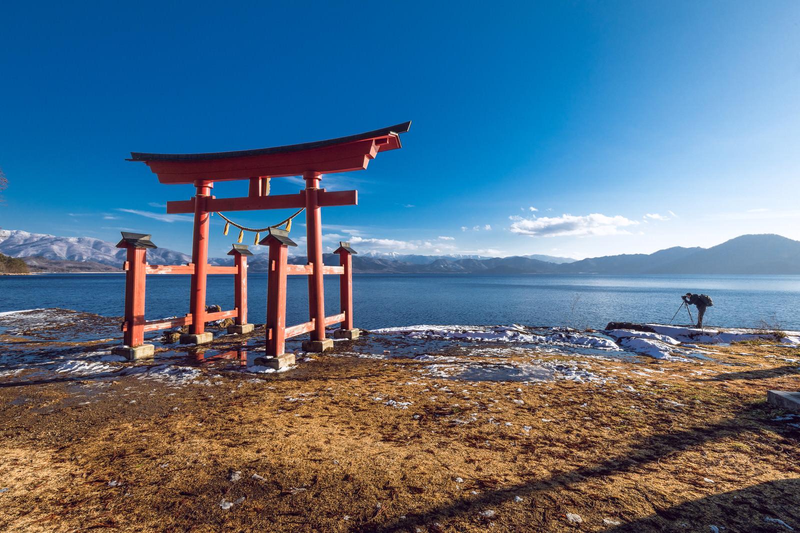 「田沢湖畔に立つ鳥居とカメラマン(秋田県仙北市)」の写真