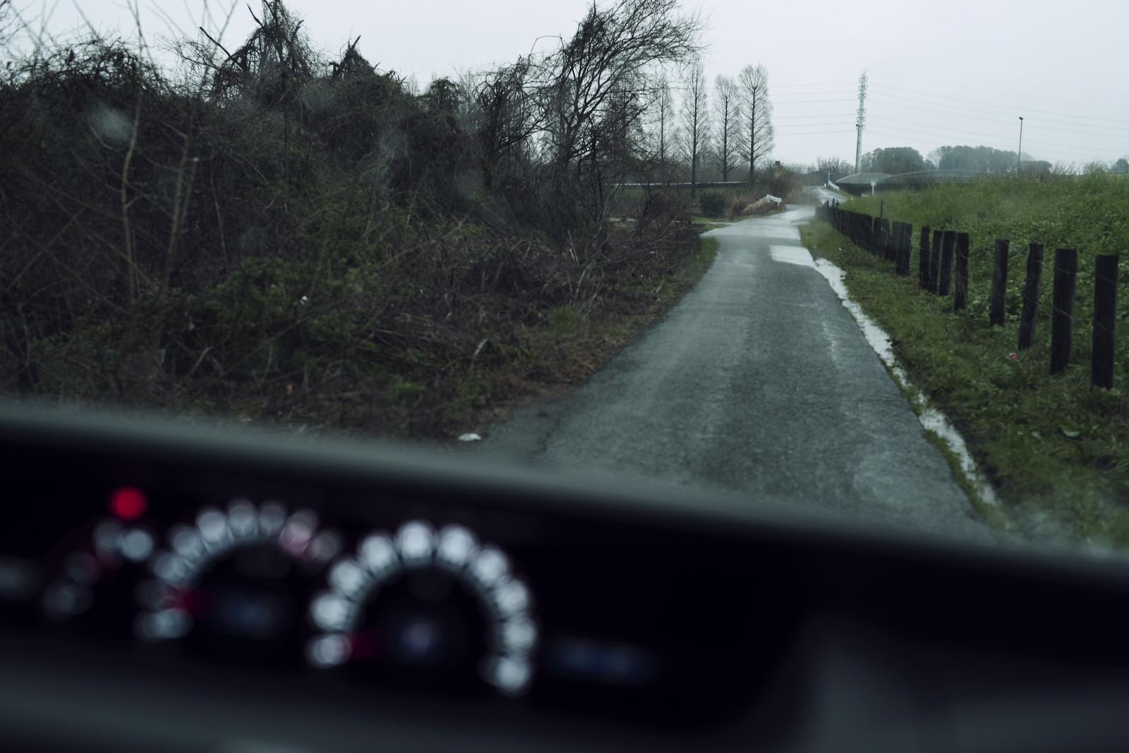 「雨の中の農道を走る車から見た景色」の写真