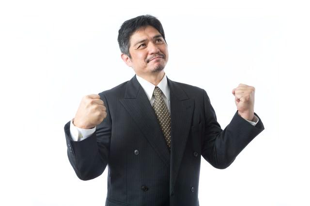 受注が決まり1人ガッツポーズを決めた上司の写真