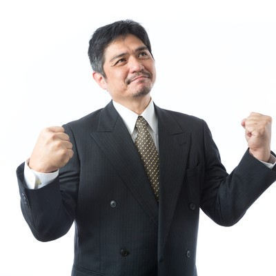「受注が決まり1人ガッツポーズを決めた上司」の写真素材