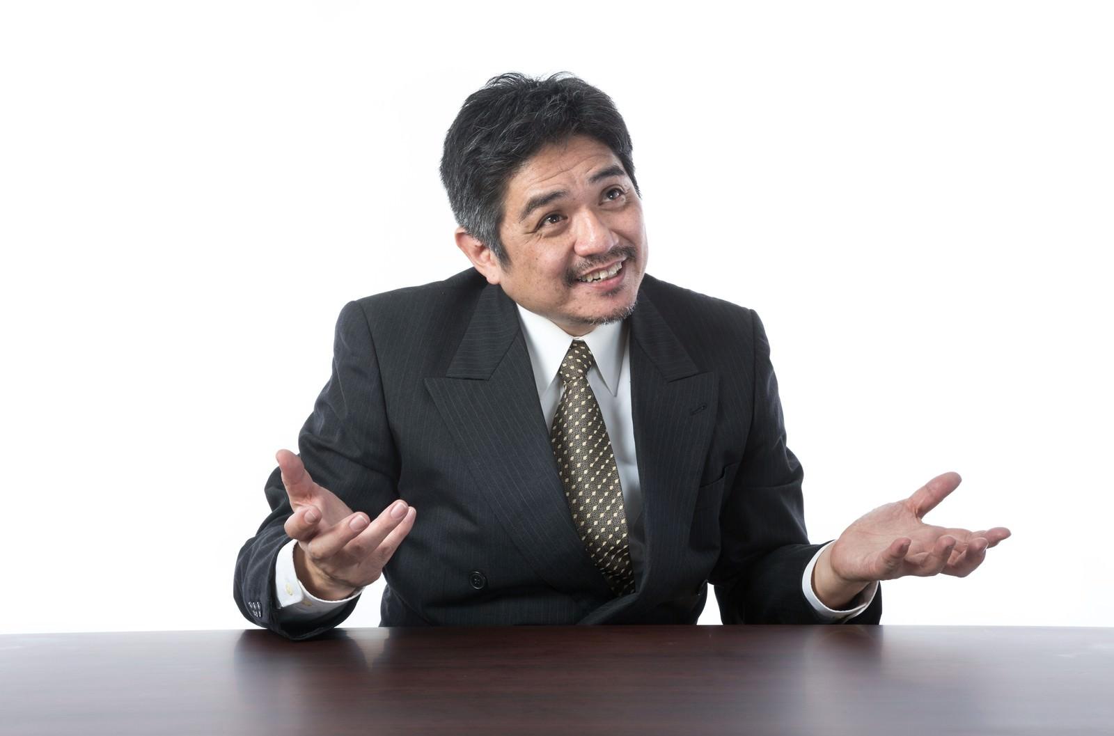 「笑顔で説明するスーツ姿の年配上司」の写真[モデル:よたか]