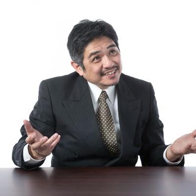 「笑顔で説明するスーツ姿の年配上司」の写真素材