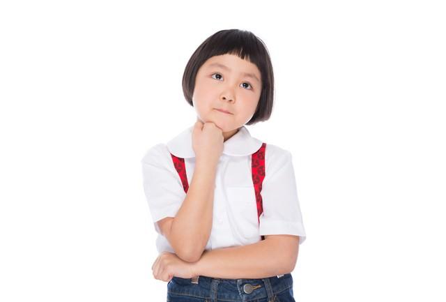 遠足のおやつを考える小学生の女の子の写真