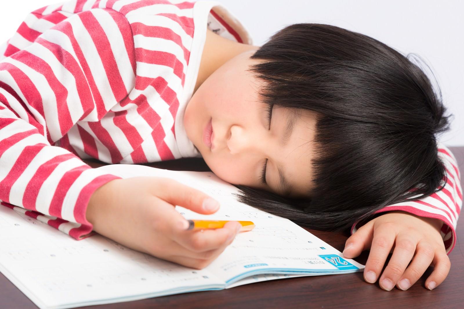 「宿題しながら爆睡する前髪パッツンの女の子」の写真[モデル:ゆうき]
