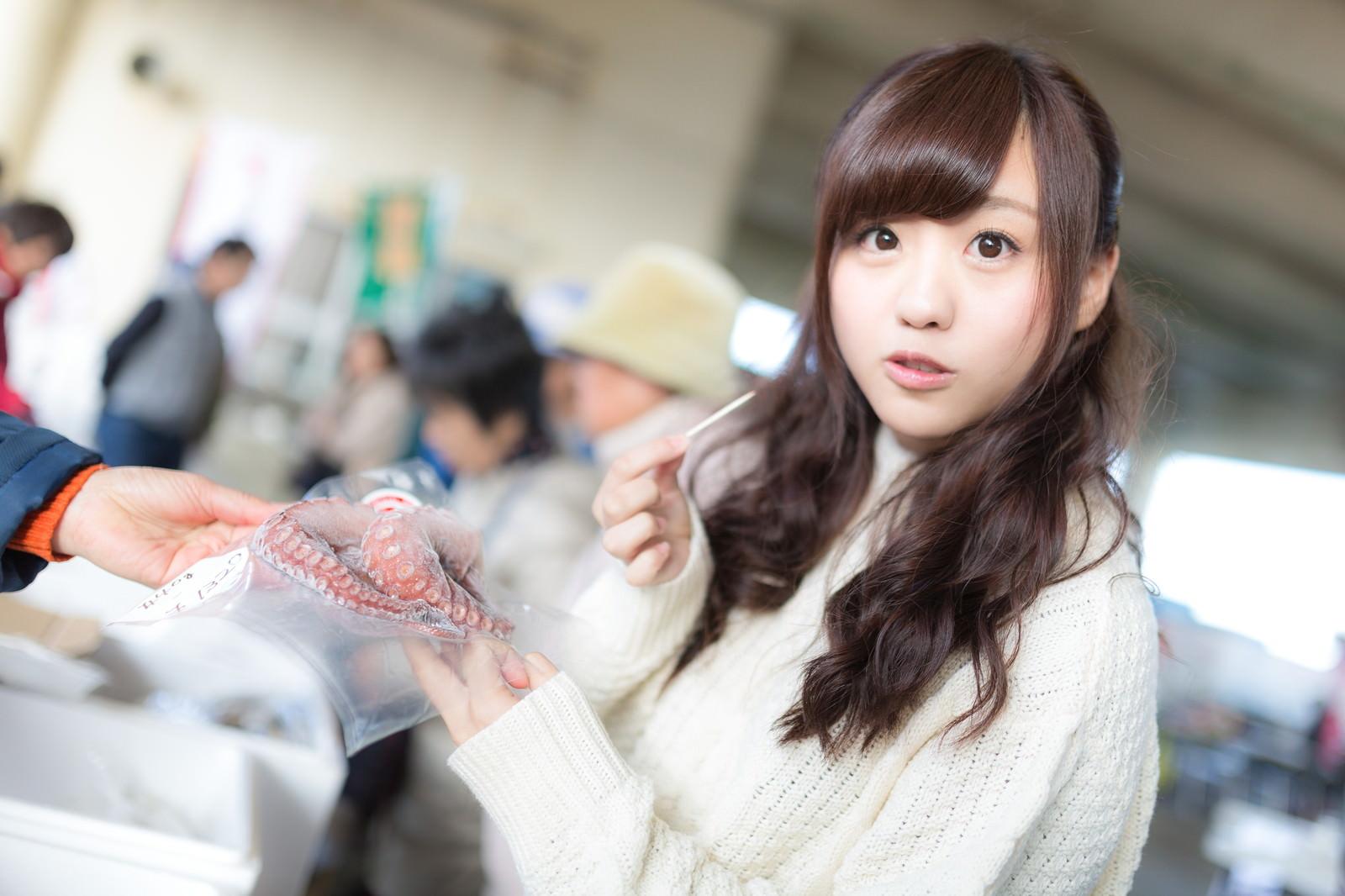 「朝市で新鮮なタコを試食する女性」の写真[モデル:河村友歌]
