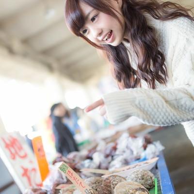 「朝市の魚介類を見て喜ぶ若い女性」の写真素材