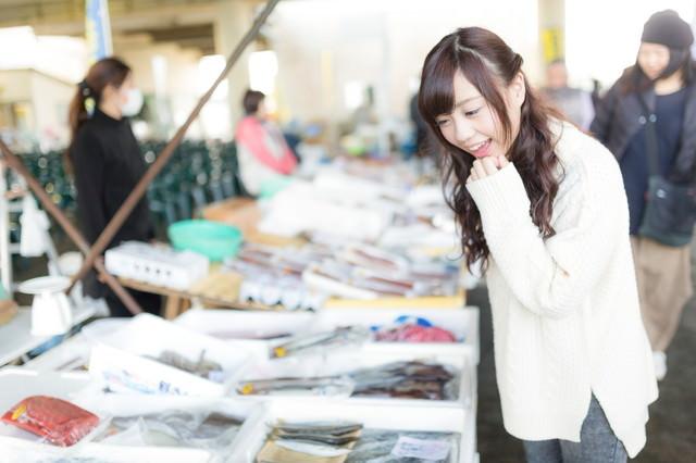 朝市の新鮮な魚を見て回る女性の写真