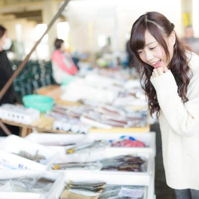 「朝市の新鮮な魚を見て回る女性」の写真素材