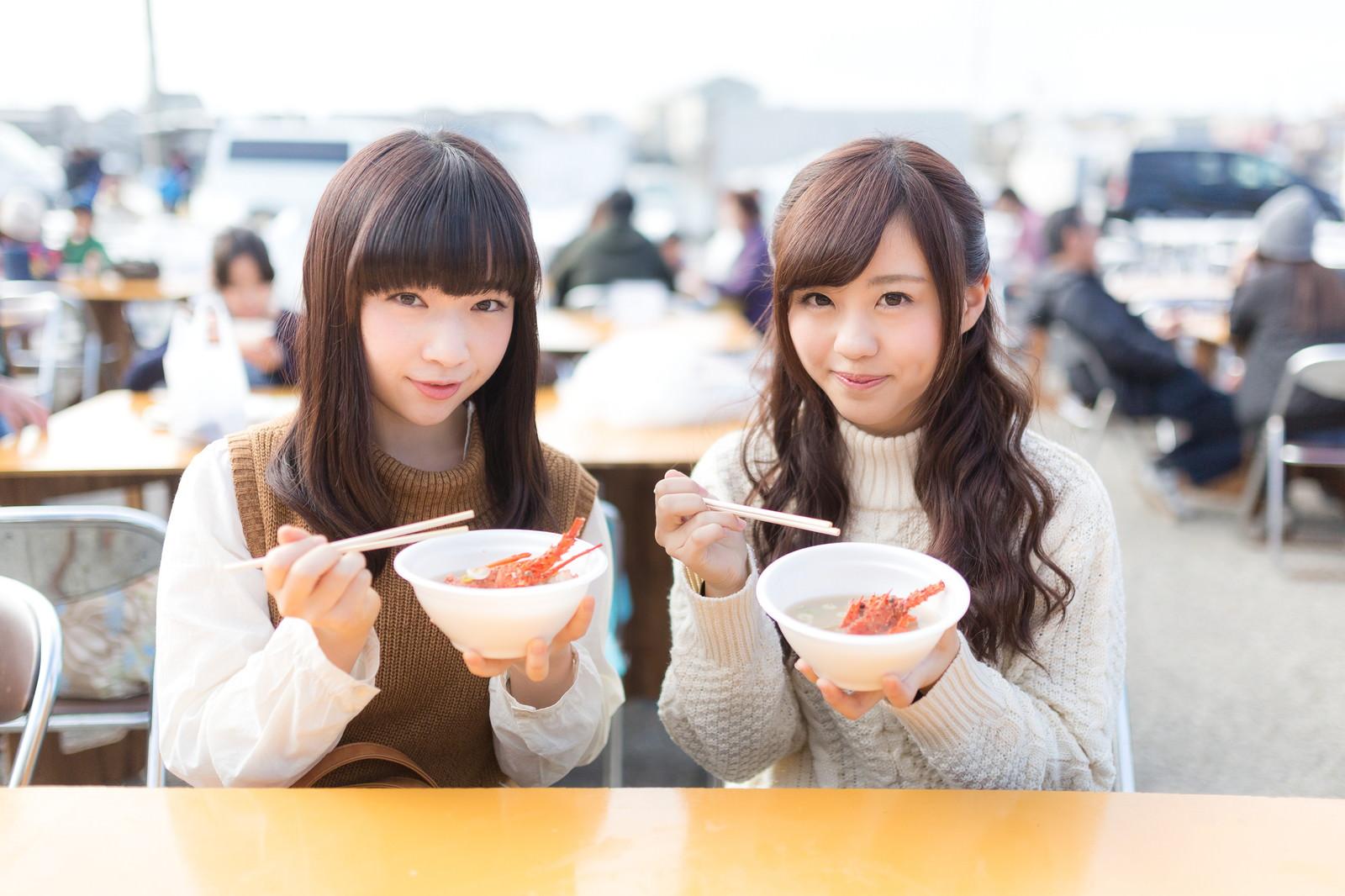 「朝市でイセエビの味噌汁を食べる女性観光客」の写真[モデル:河村友歌 渡辺友美子]