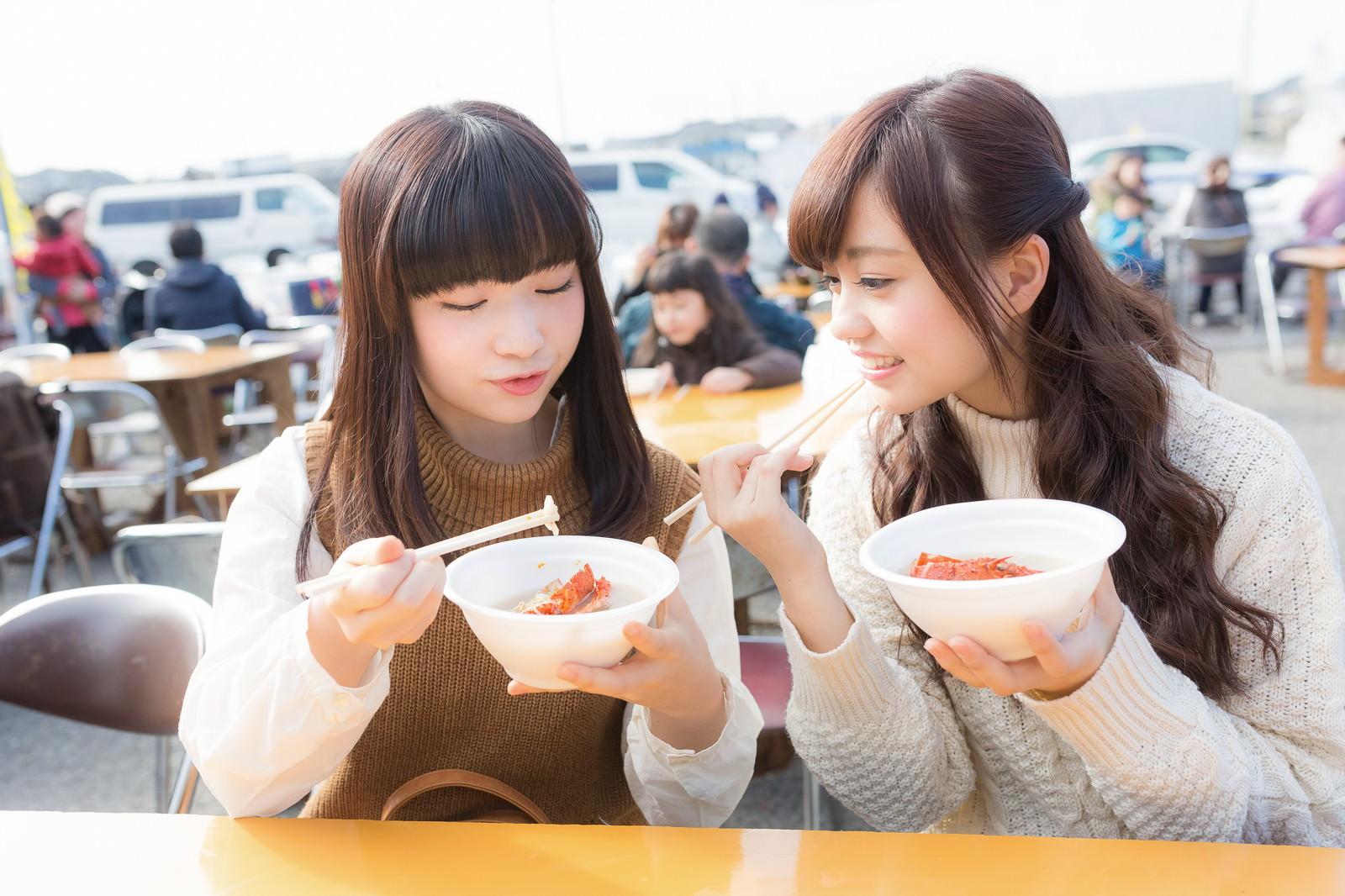 「朝市のフードコートで伊勢海老のお吸い物を食べる女性二人」の写真[モデル:渡辺友美子 河村友歌]