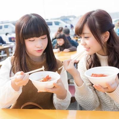 「朝市のフードコートで伊勢海老のお吸い物を食べる女性二人」の写真素材