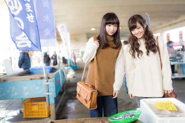 市場で地元の特産品を見て回る女性観光客の写真