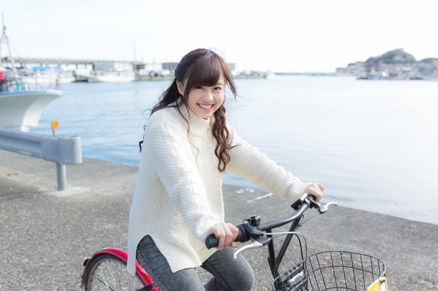 自転車にのってはしゃぐ彼女の写真