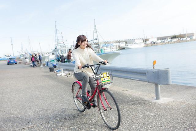 レンタサイクルで漁港を走る女性観光客の写真