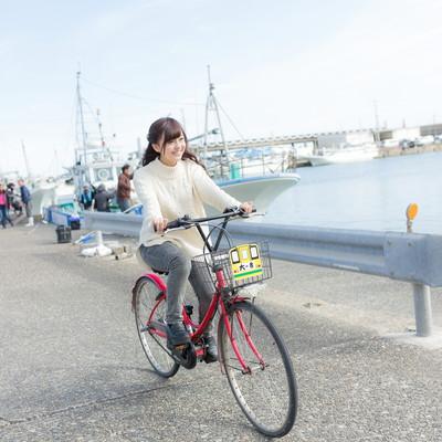 「レンタサイクルで漁港を走る女性観光客」の写真素材