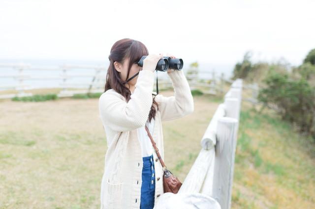 双眼鏡で景色を眺めるする女性の写真