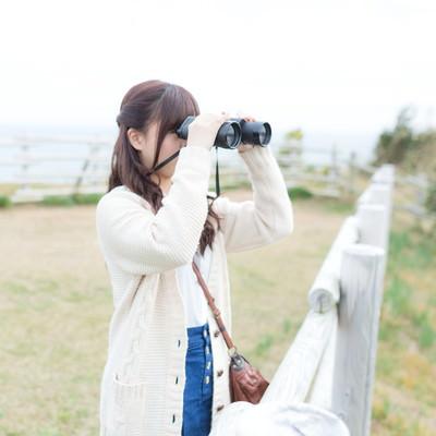 「双眼鏡で景色を眺めるする女性」の写真素材