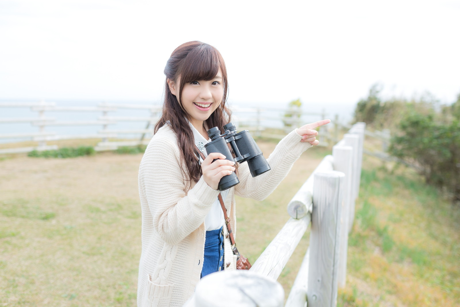 「笑顔で観光地を案内する双眼鏡女子」の写真[モデル:河村友歌]