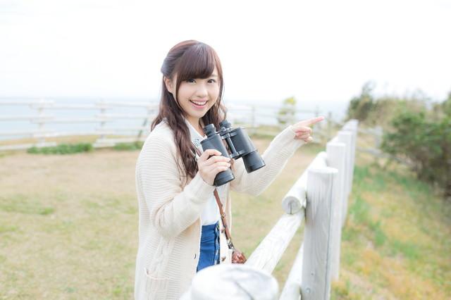 笑顔で観光地を案内する双眼鏡女子の写真
