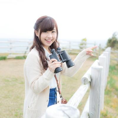 「笑顔で観光地を案内する双眼鏡女子」の写真素材