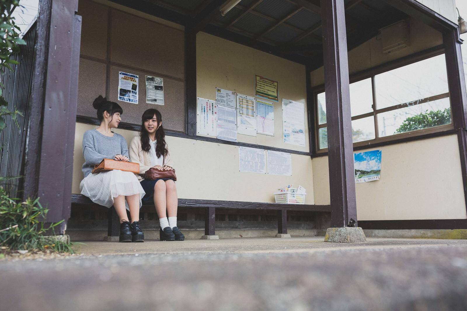 「電車の待ち時間に旅の思い出を共有する女性観光客」の写真[モデル:河村友歌 渡辺友美子]