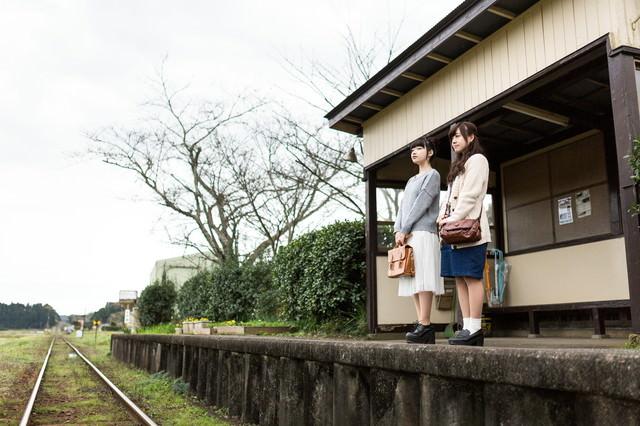 無人駅で電車を待つ女性の写真