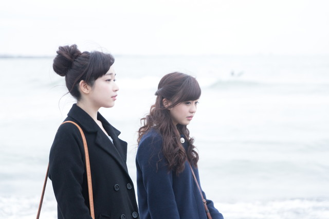 女性二人で冬の海を歩くの写真