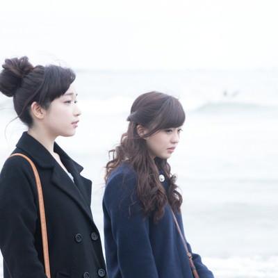 「女性二人で冬の海を歩く」の写真素材