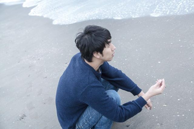 砂浜で思いをはせる男性の写真
