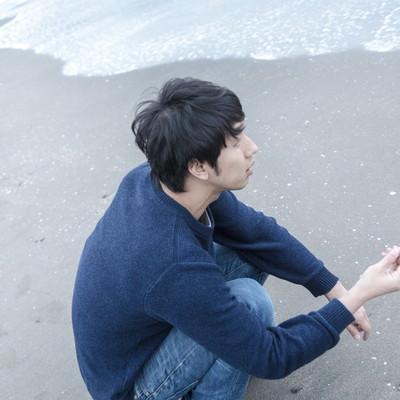 「砂浜で思いをはせる男性」の写真素材