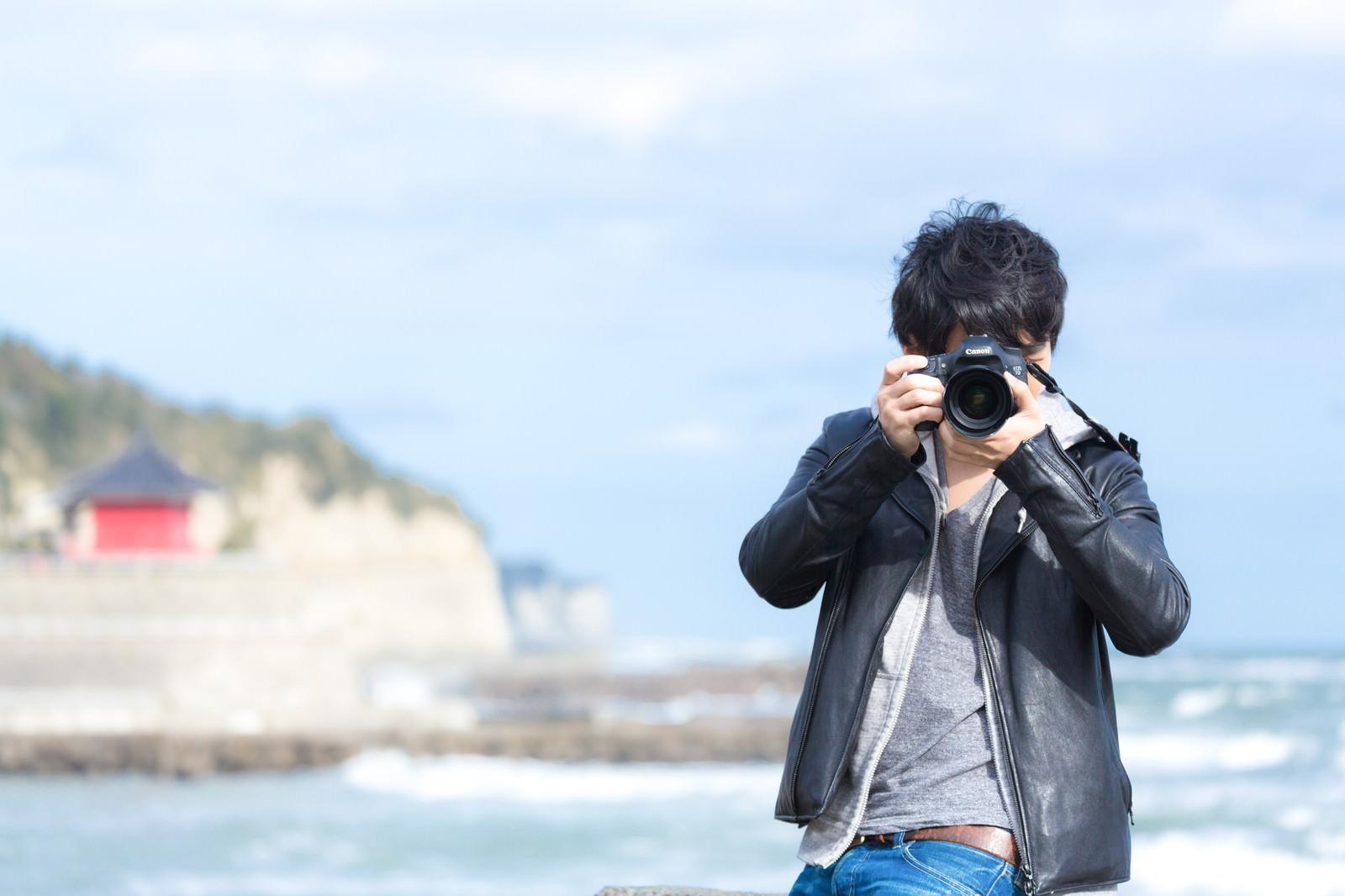 「海岸でカメラを構える男性」の写真[モデル:大川竜弥]