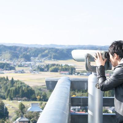 「双眼鏡を覗き込む男性観光客」の写真素材