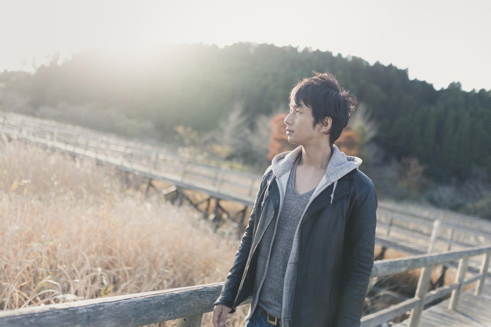 「夕暮れどきトンボの沼を散歩する男性」の写真[モデル:大川竜弥]