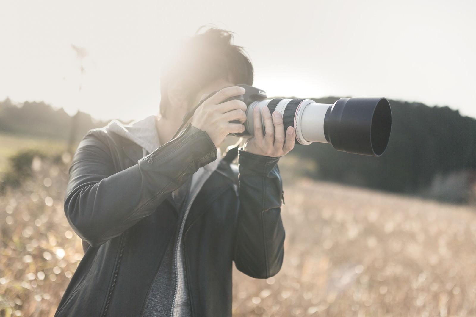 「望遠レンズで風景を撮影するカメラマン」の写真[モデル:大川竜弥]