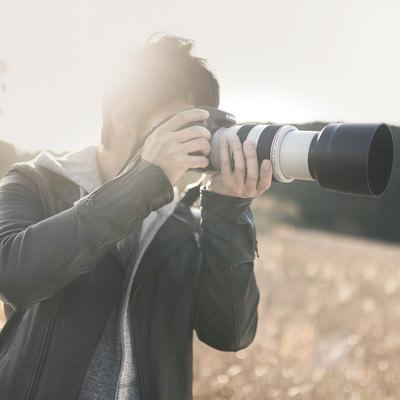 「望遠レンズで風景を撮影するカメラマン」の写真素材