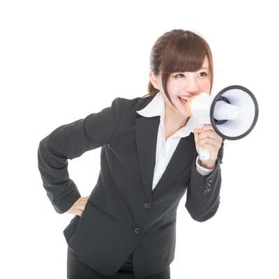 拡声器で応援する女性社員の写真